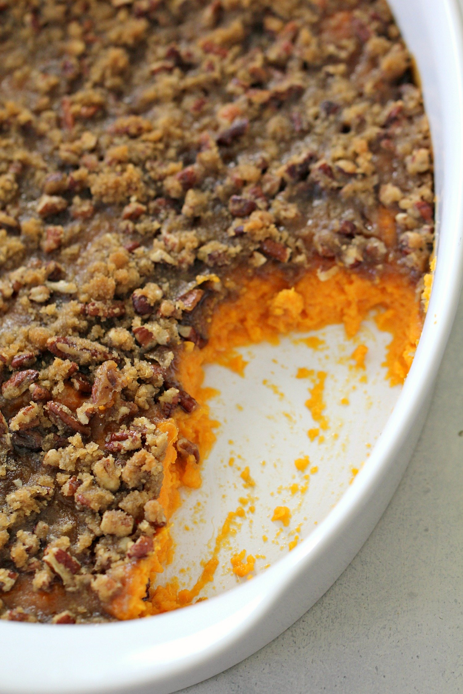 sweet potato casserole with pecan brown sugar topping in a large white pan