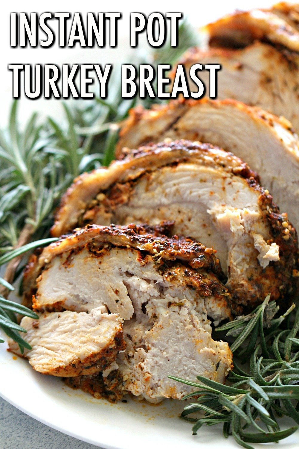 Instant Pot Turkey Breast cooked and ready to serve on a plate of rosemary.