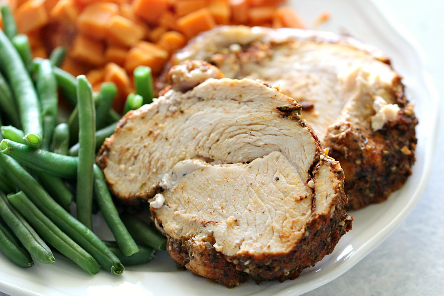 Instant Pot Turkey Breast cooked, sliced, and ready to serve on a plate of green beans and sweet potatoes