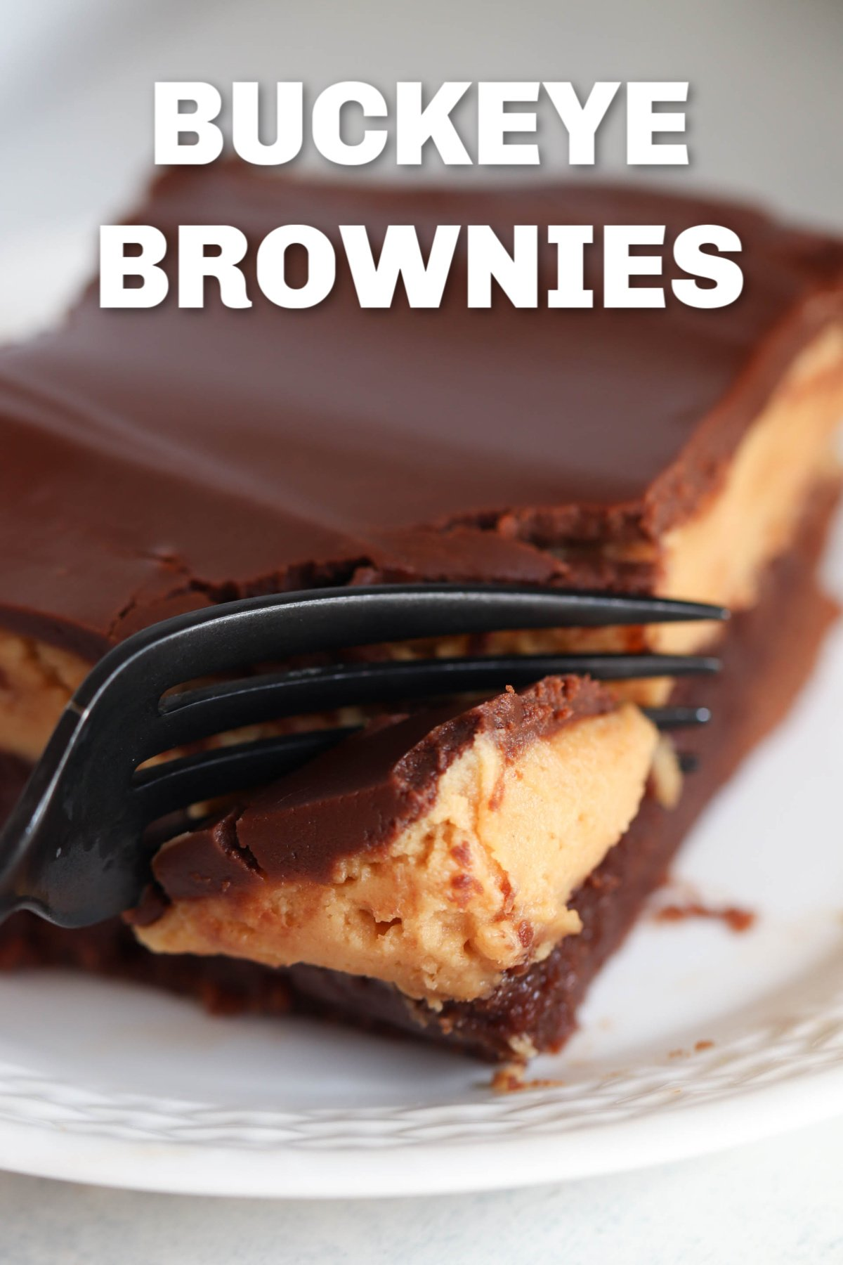 One Buckeye Brownie square on a white plate with a fork