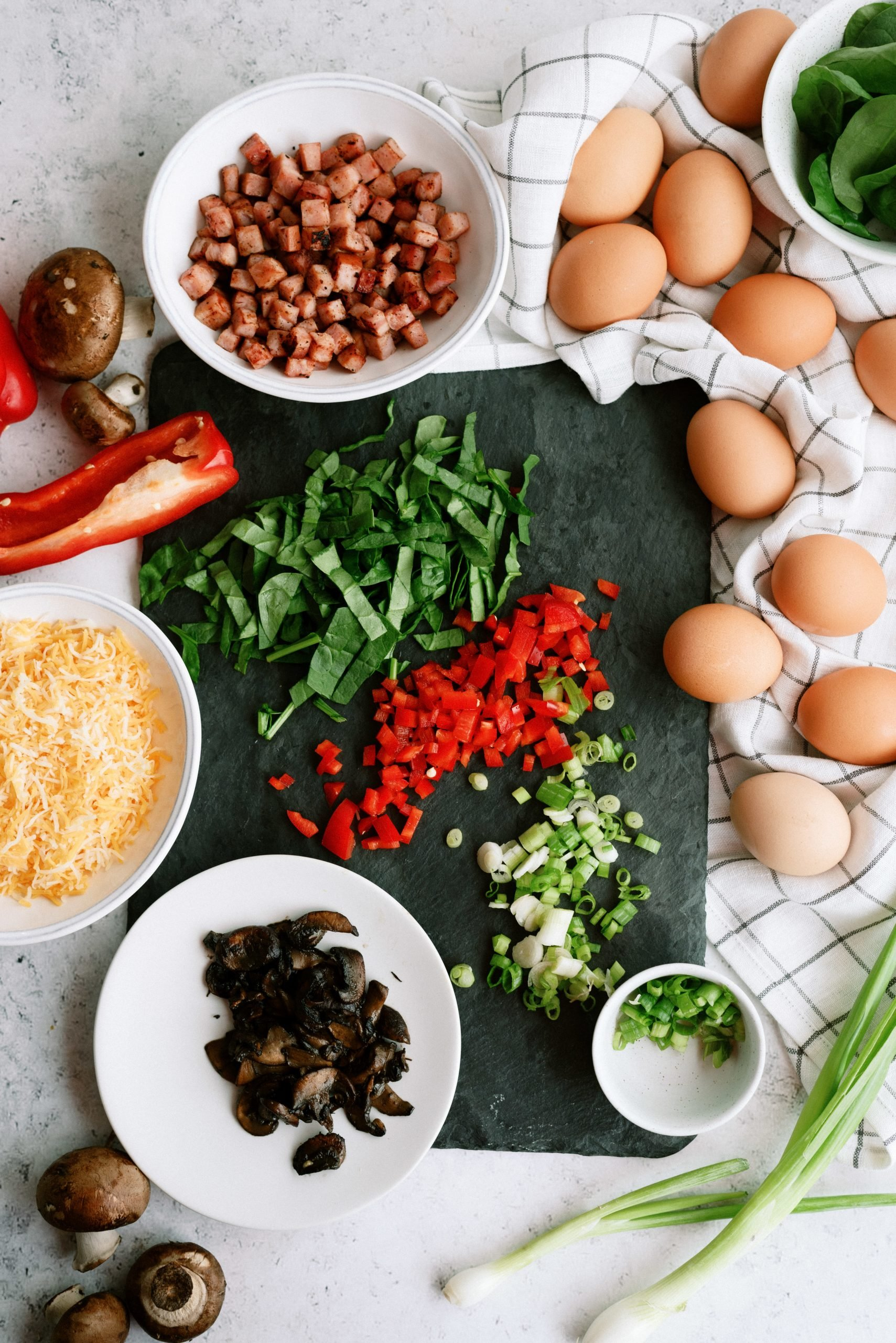 Chopped ingredients for scrambled egg breakfast muffins - ham, pepper, eggs, onion, mushrooms, spinach, and cheese