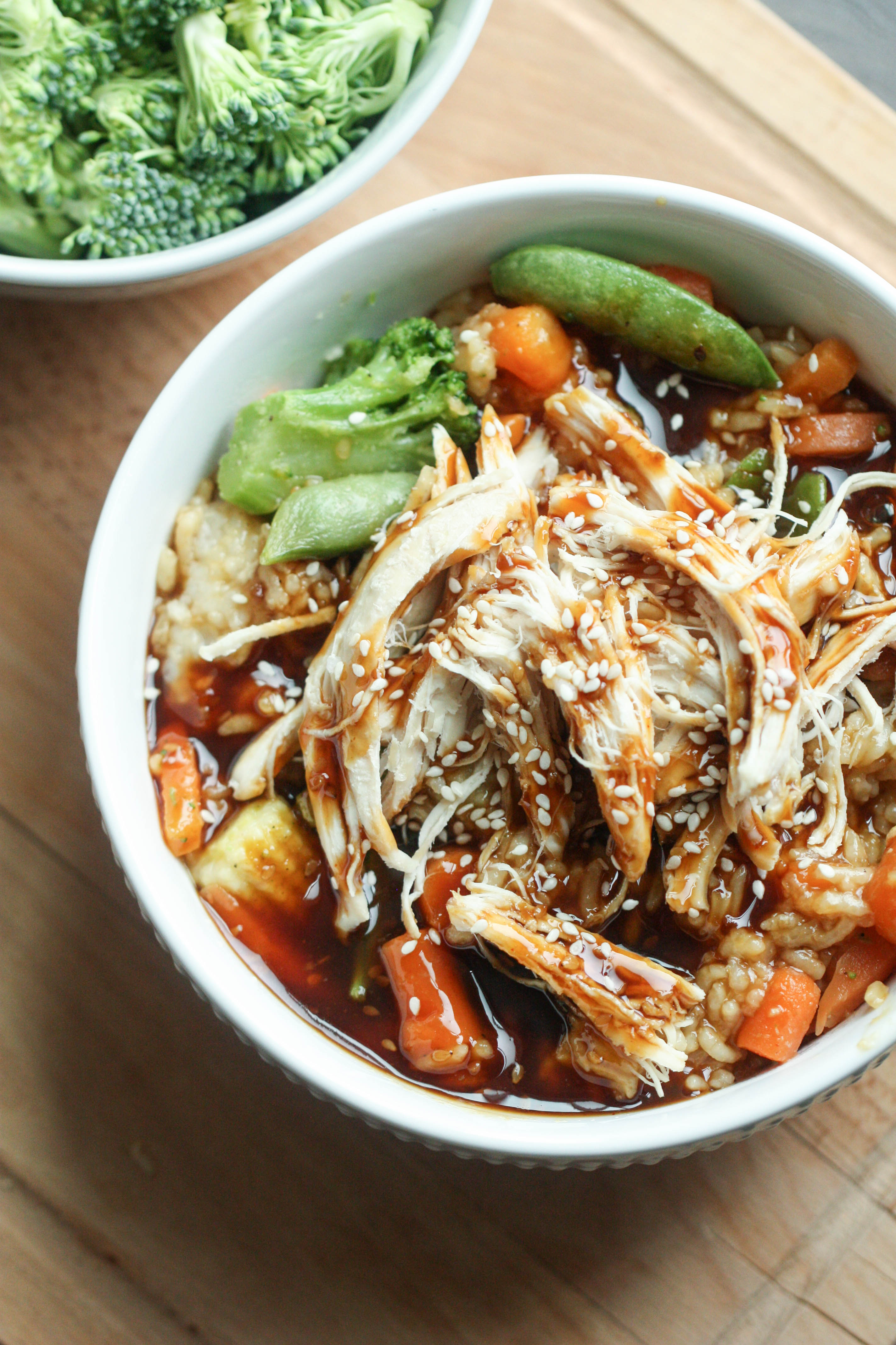 Teriyaki Chicken Bowls assembled with rice on the bottom, veggies in the middl, and chicken drizzled with extra teriyaki sauce and sesame seeds on top.