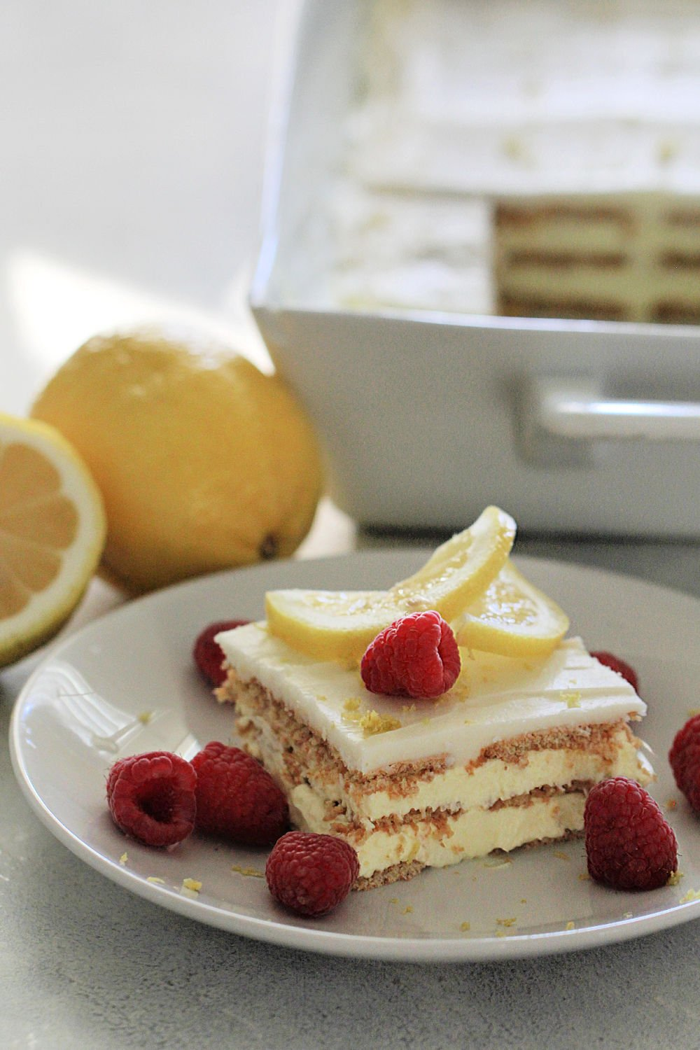 No Bake Lemon Ice Box Cake Recipe (Eclair Cake) on a white plate topped with lemon slices and raspberries