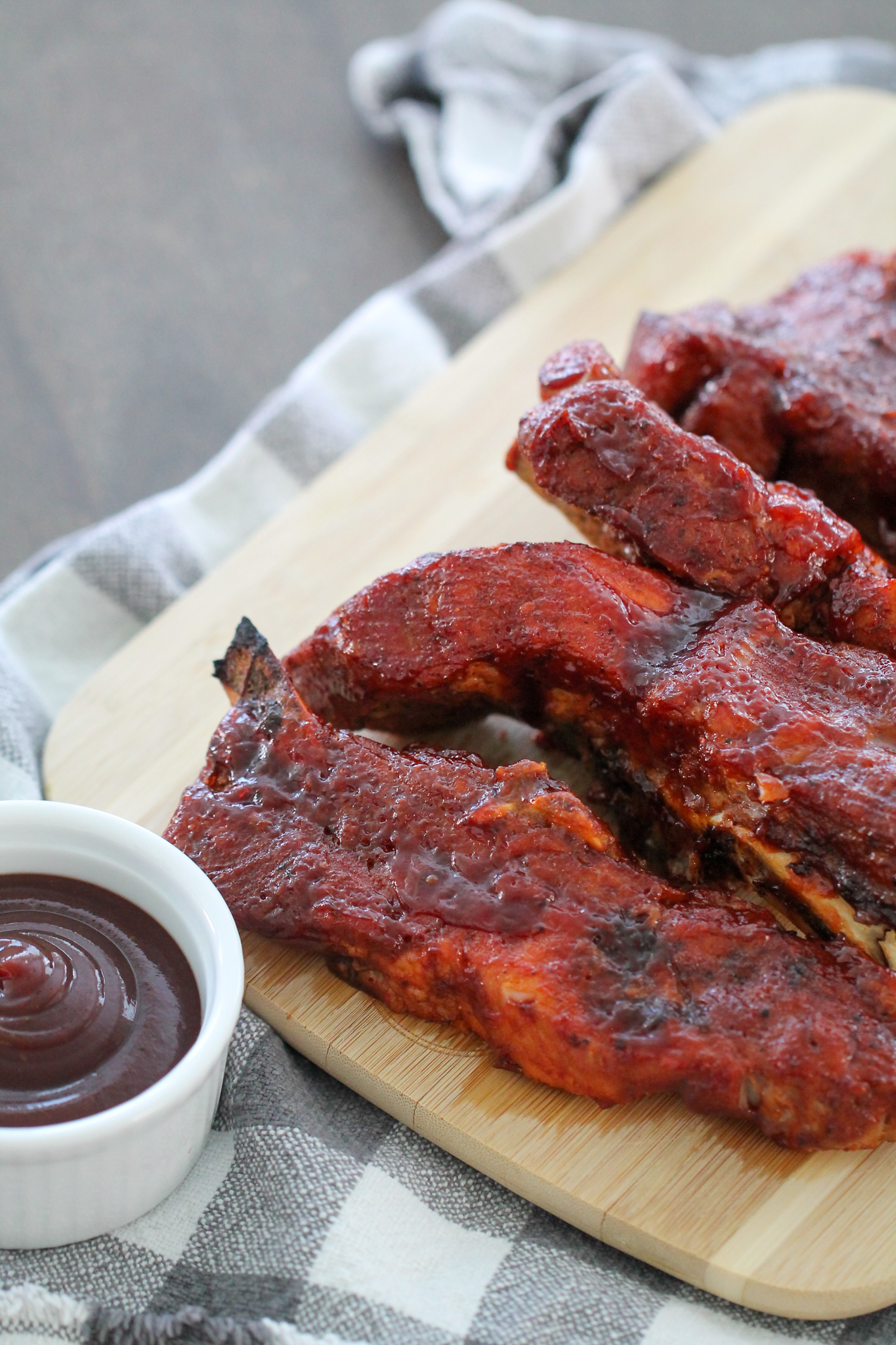 Instant Pot BBQ Country Ribs on a wooden cutting board with a side of BBQ Sauce