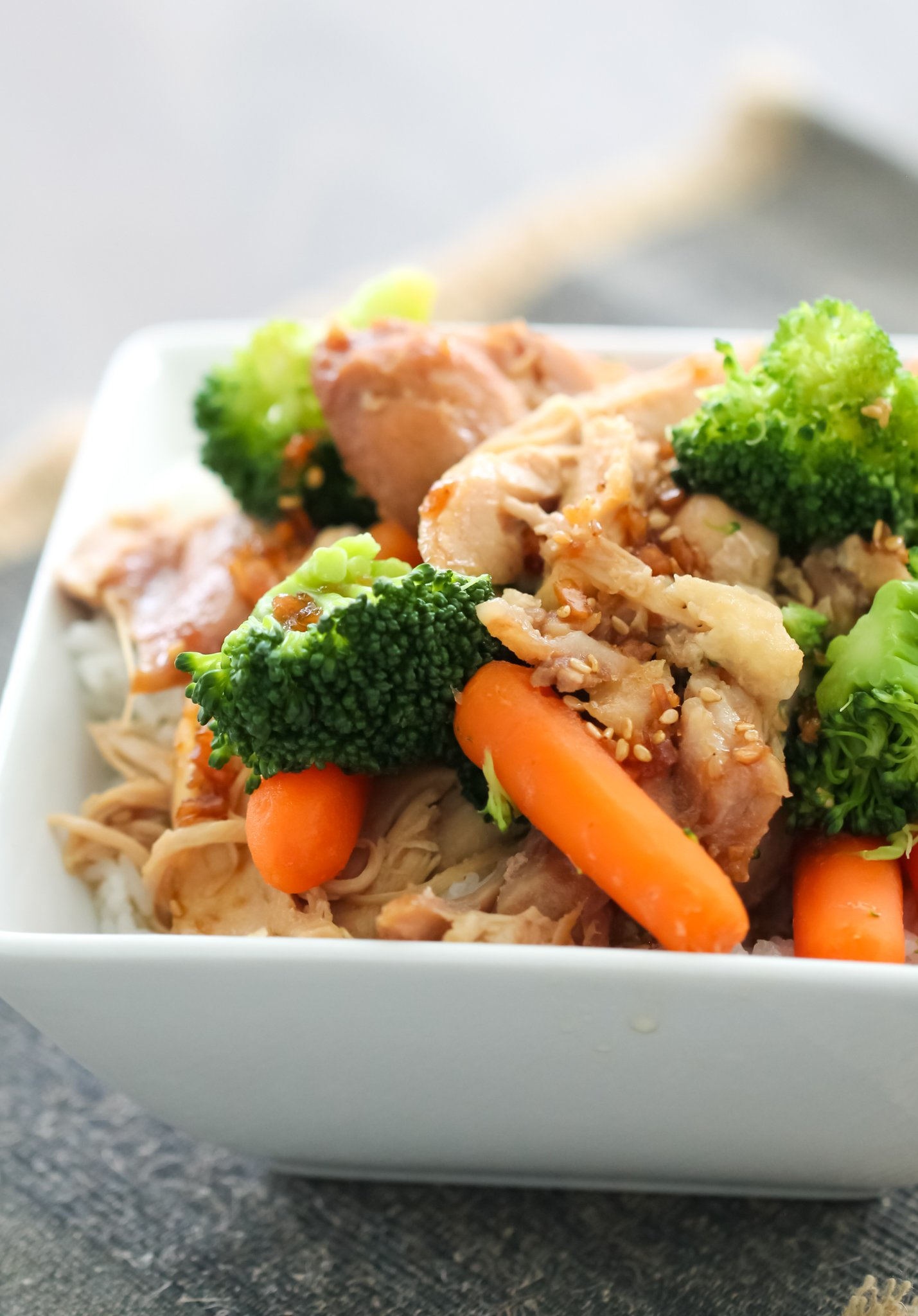 Slow Cooker Teriyaki Chicken in a white bowl with carrots and broccoli