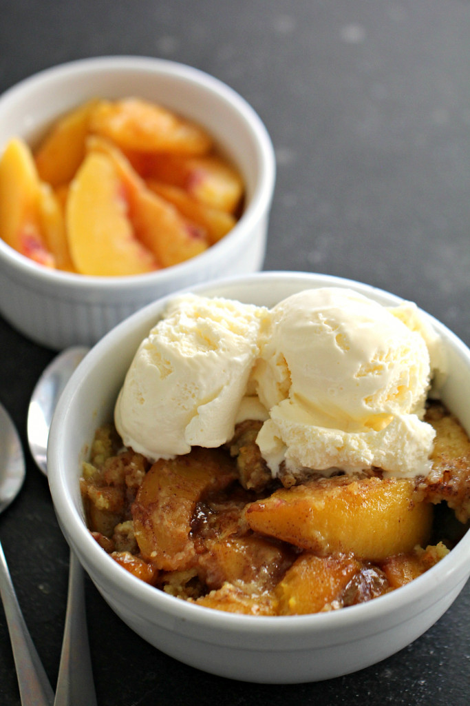 peach cobbler topped with ice cream in a white bowl