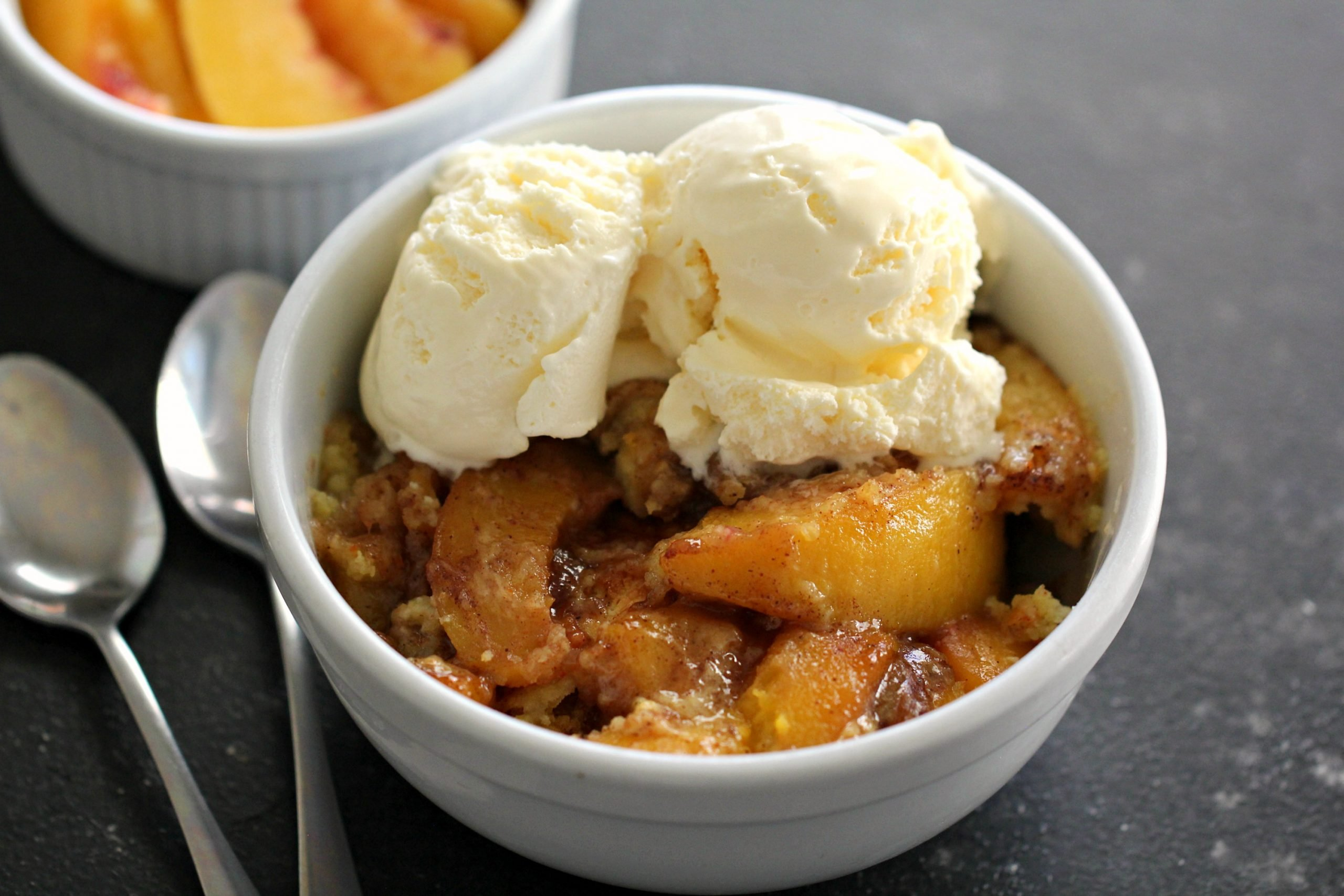 Easy Instant Pot Peach Cobbler in a white bowl topped with ice cream
