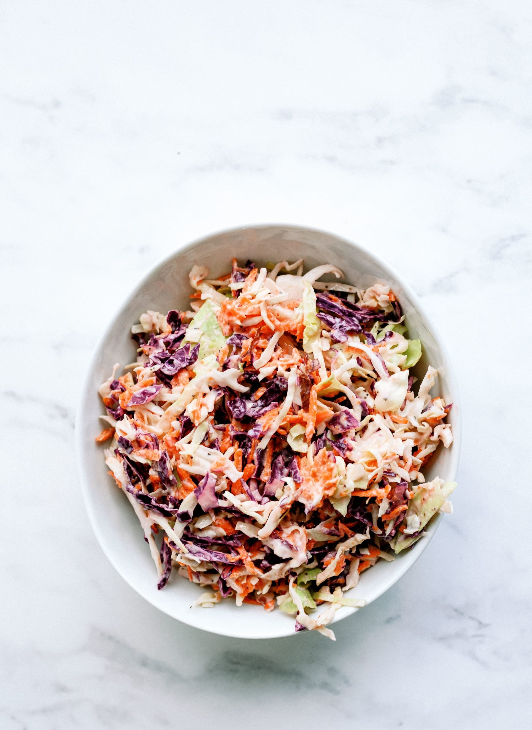 purple cabbage, shredded carrots, and green cabbage coleslaw in a bowl