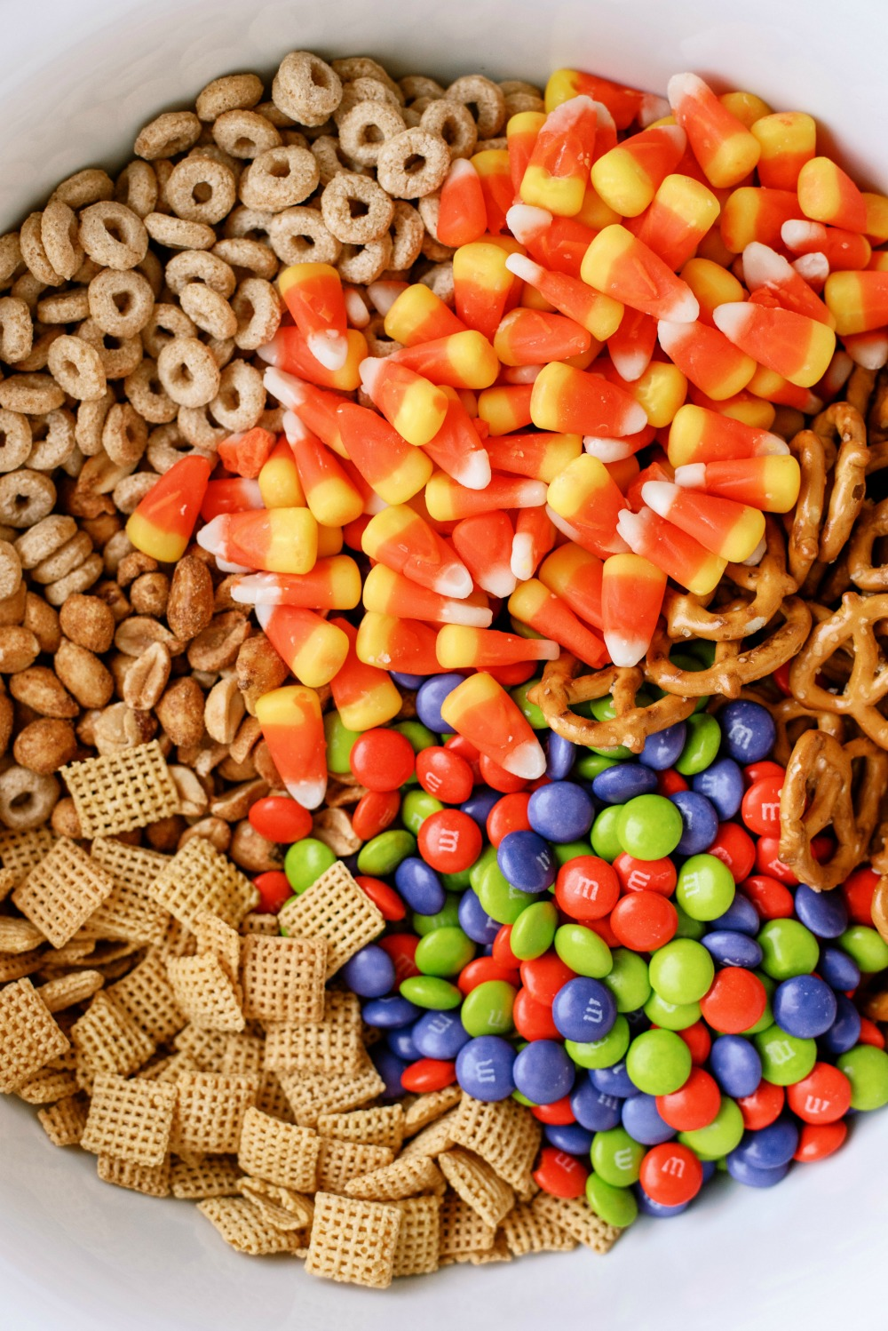 Ingredients for chex mix monster munch dumped into a bowl