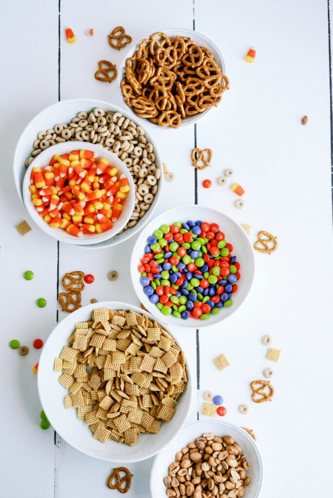 Cheerios, candy corn, m&m candies, chex mix, and peanuts in bowls