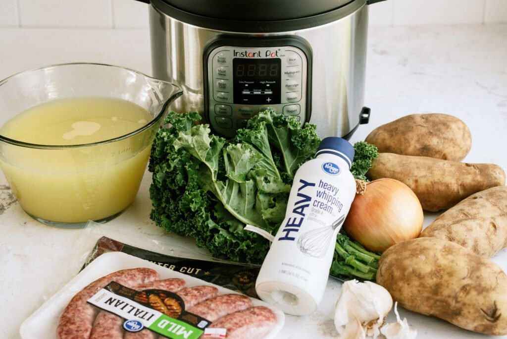 Raw ingredients for Instant Pot Zuppa Toscana: chicken broth, kale, onion, garlic, potatoes, sausage, bacon, and cream.