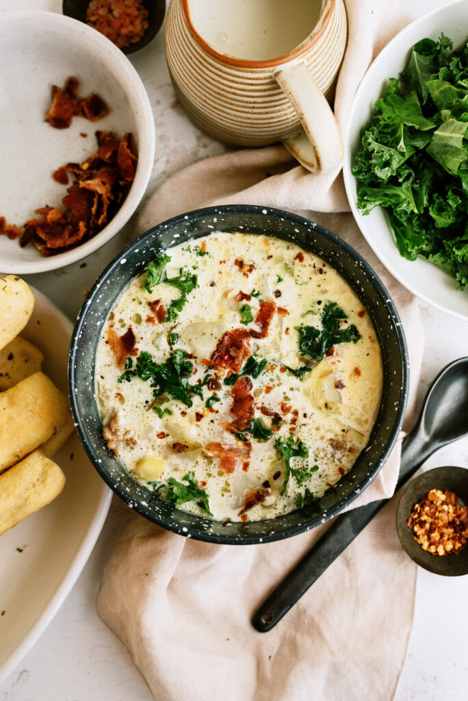 Instant Pot Zuppa Toscana in a serving bowl, with a side of breadsticks and ingredients showcased around the bowl.