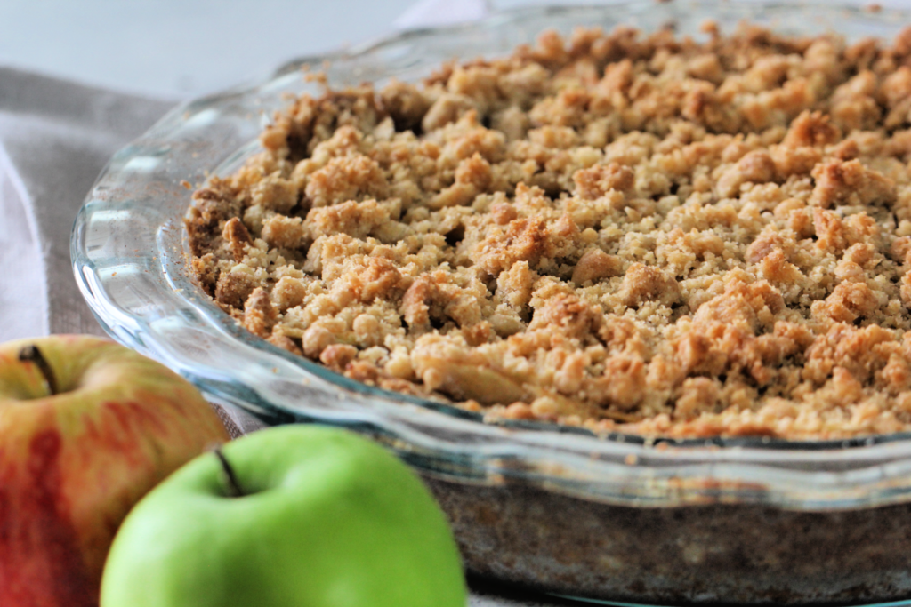 dutch apple pie in a glass pie pan with red and green apple in the corner