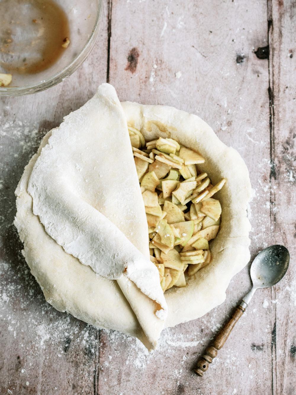 sliced apples inside pie dough to make an apple pie