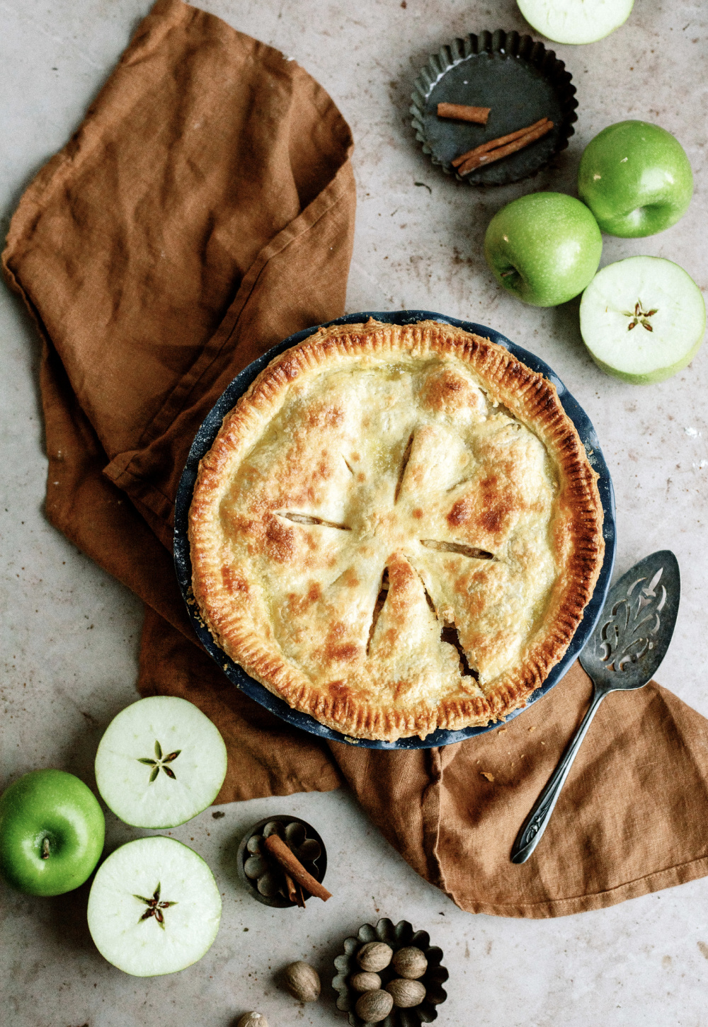 freshly baked apple pie in pie in surrounded by green apples