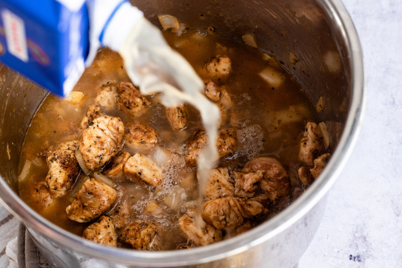 chicken broth added to the Instant Pot with chicken and onions
