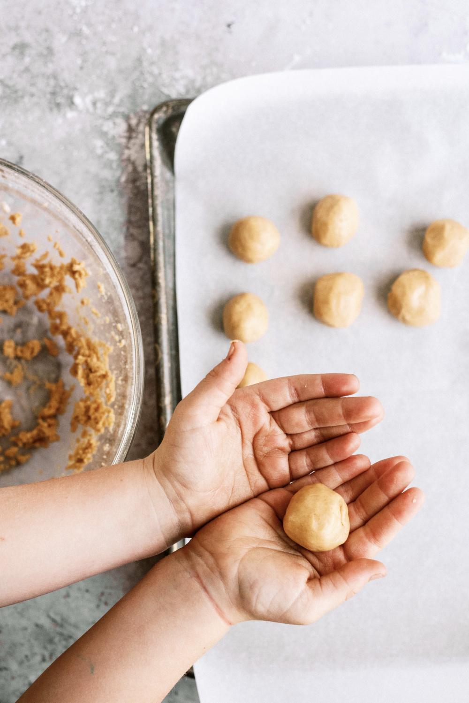 hands rolling peanut butter dough into a ball