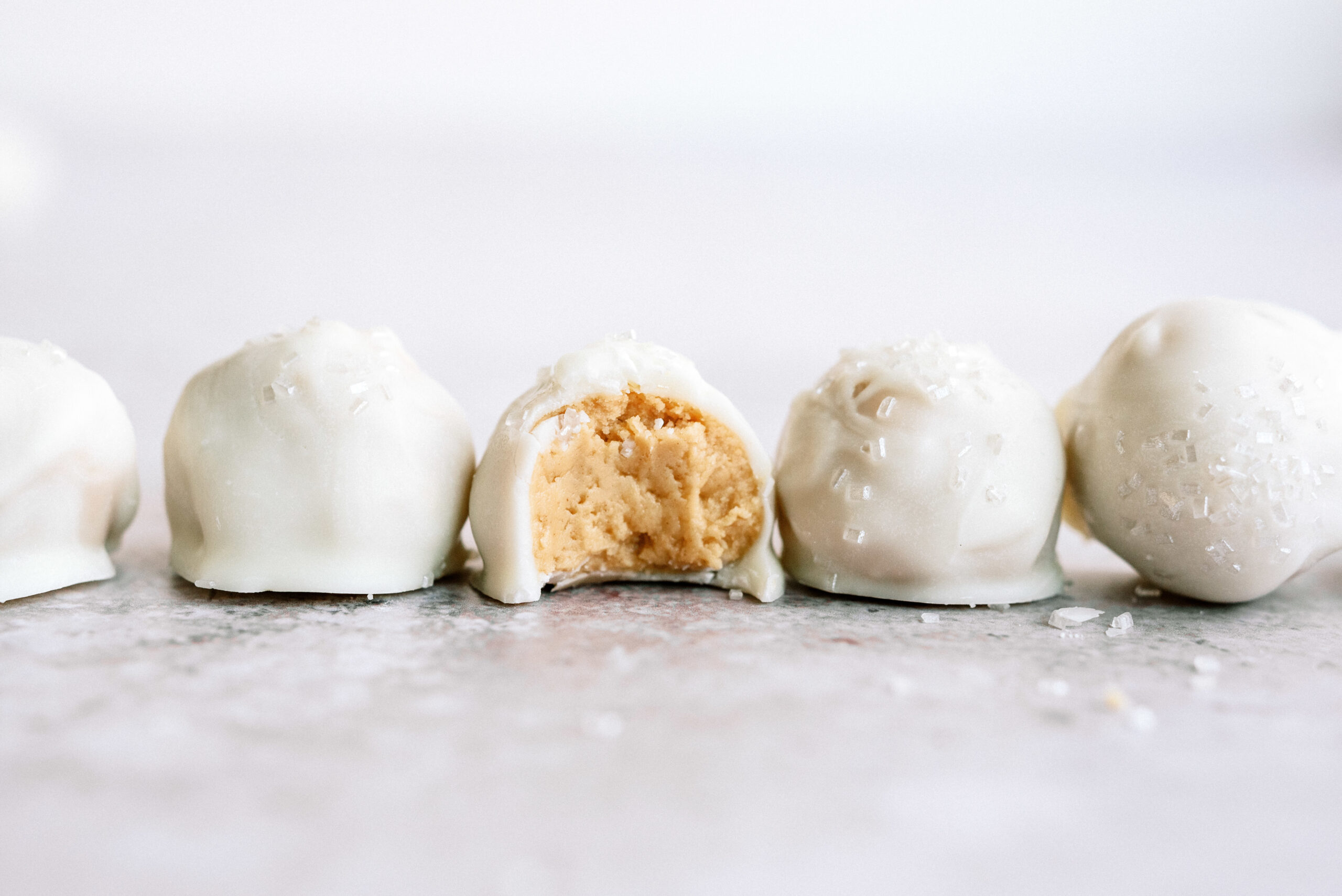 peanut butter snowballs in a line with a bite out of the middle one