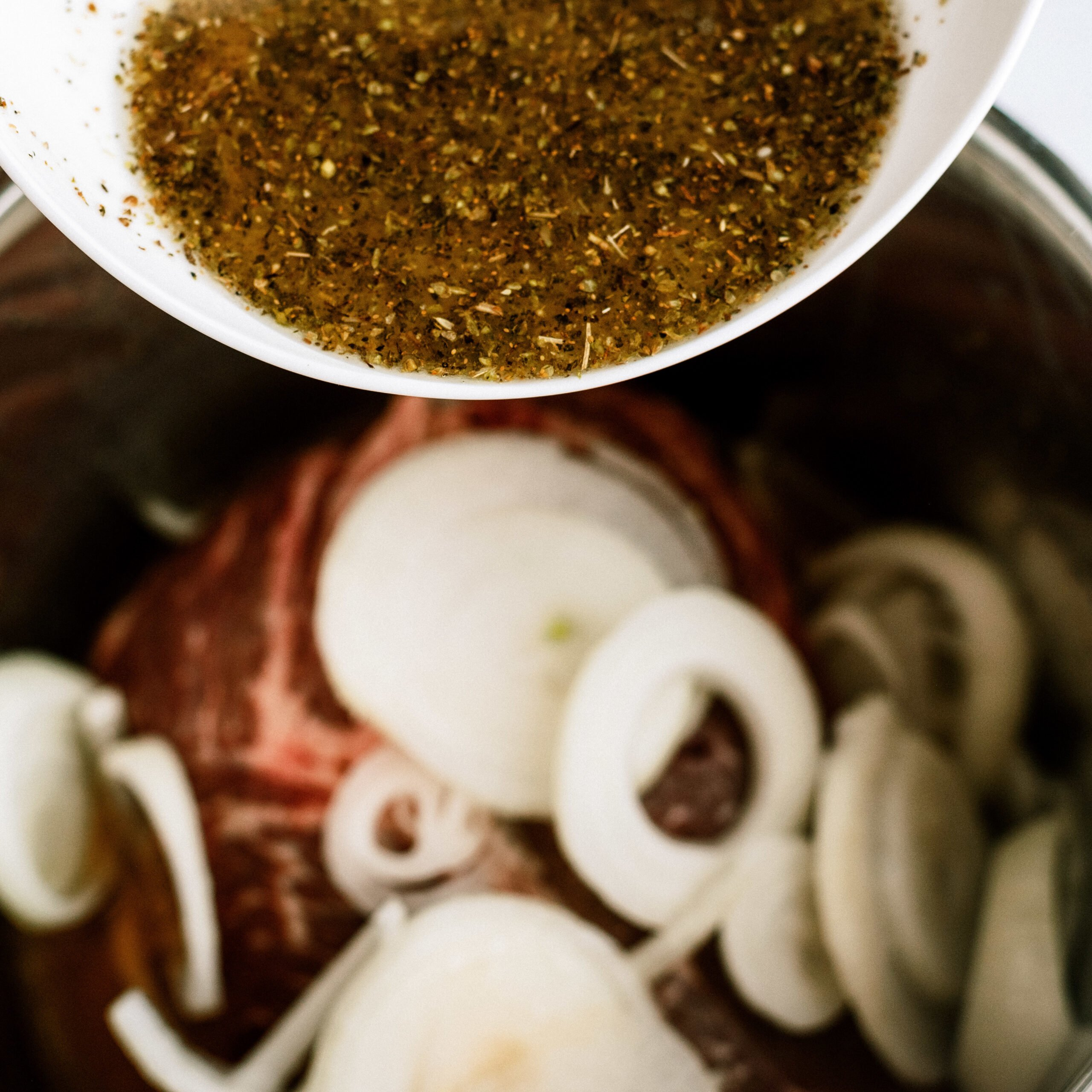 beef broth and seasonings poured on top of beef and onions in instant pot