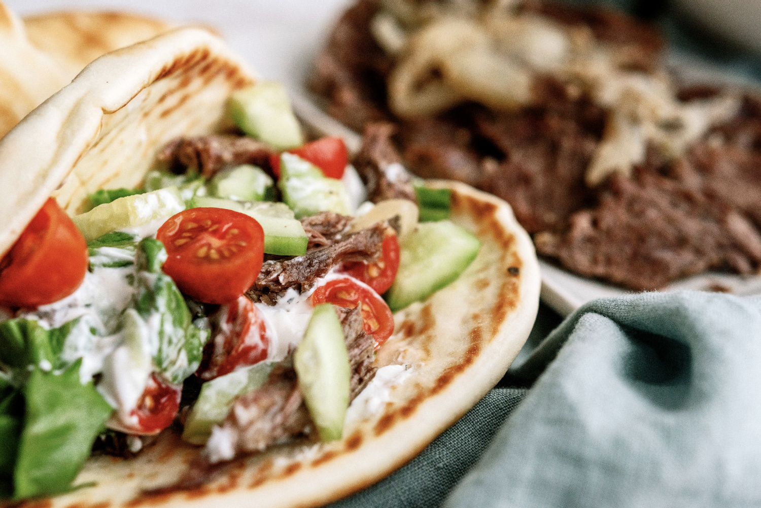 instant pot beef gyros served on pitas with tomatoes and cucumbers on top