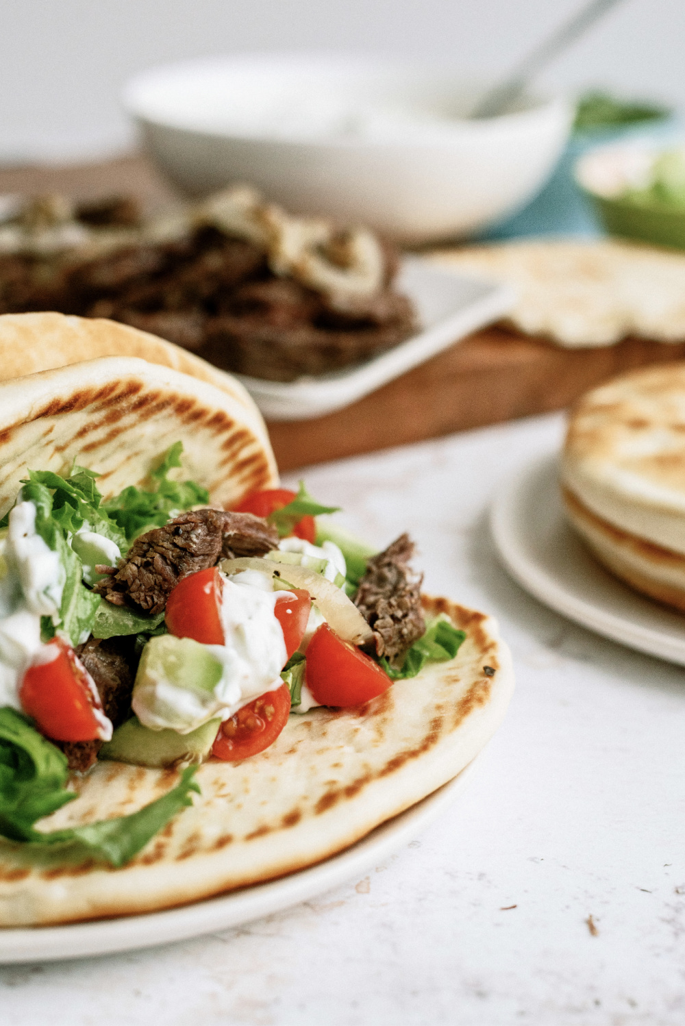 beef gyros with tomatoes and lettuce and cucumber and tzatziki
