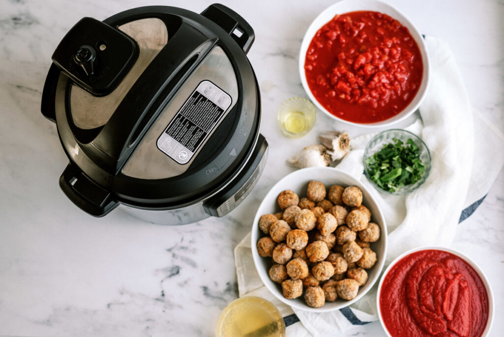 ingredients for the recipe: frozen meatballs, tomato puree, petite diced tomatoes, olive oil, minced garlic, basil, chicken broth