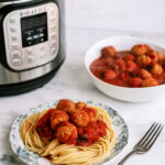 Instant Pot Italian Meatballs plated with spaghetti noodles