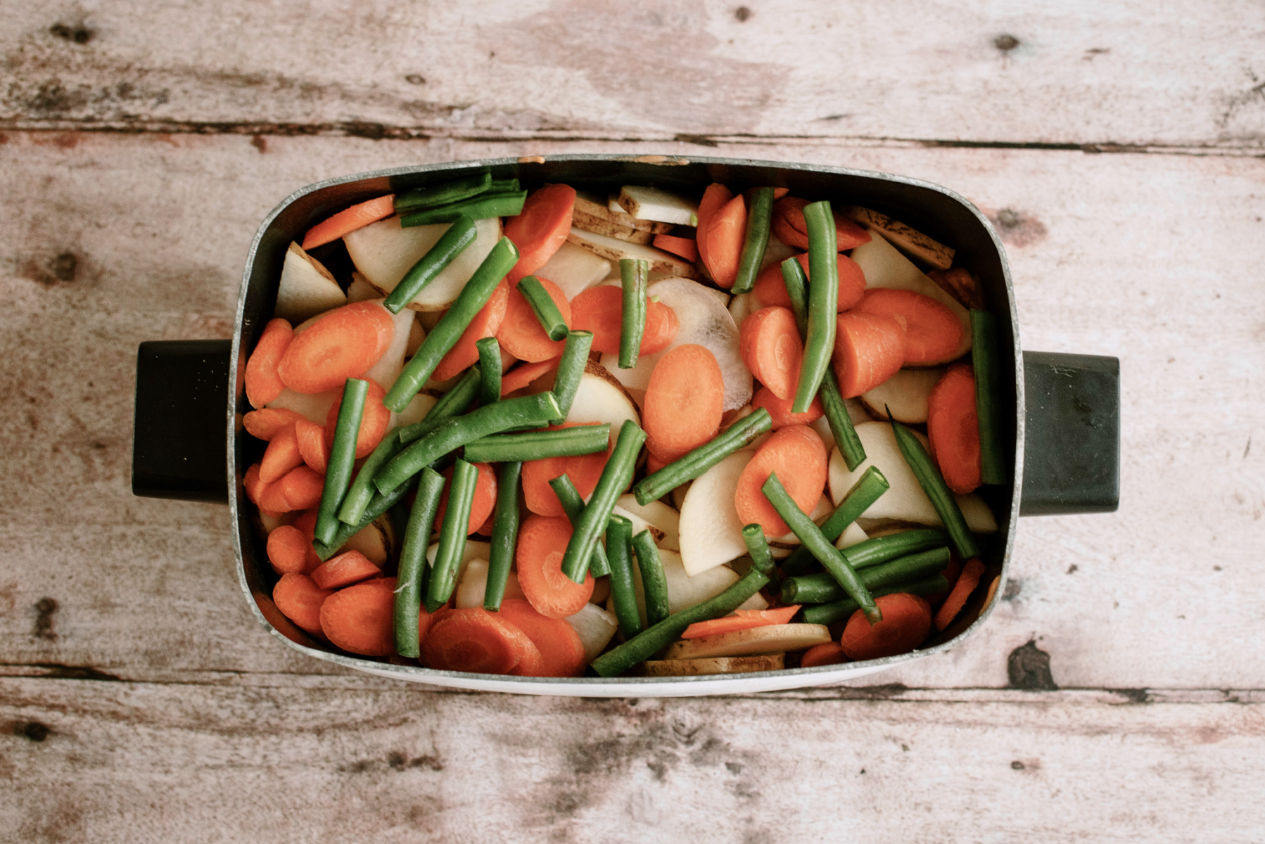 vegetables stacked in the bottom of the slow cooker