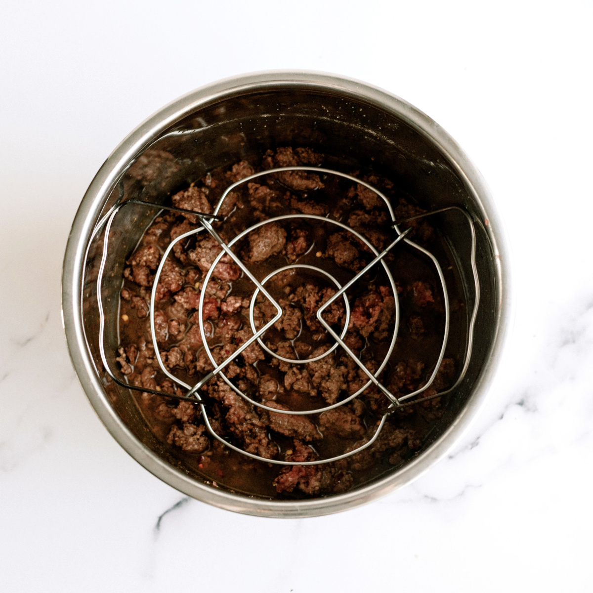 trivet placed on top of ground beef in the bottom of the instant pot