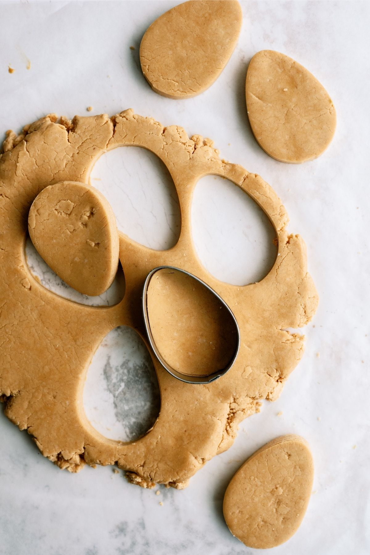 Cookie Cutter cutting out dough for Homemade Reese's Eggs in mixing bowl