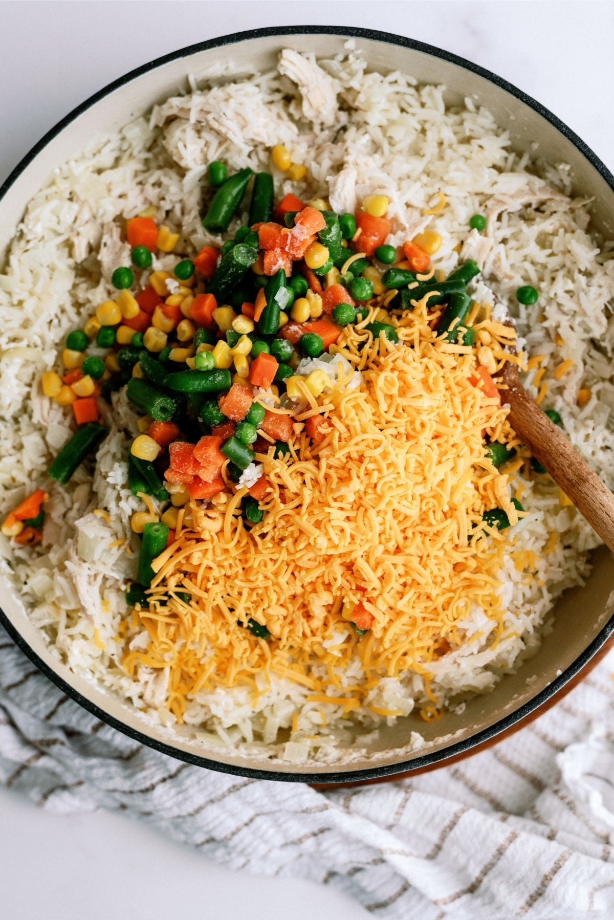 Add frozen vegetables and shredded cheese to pot for Creamy Chicken and Rice Casserole Skillet