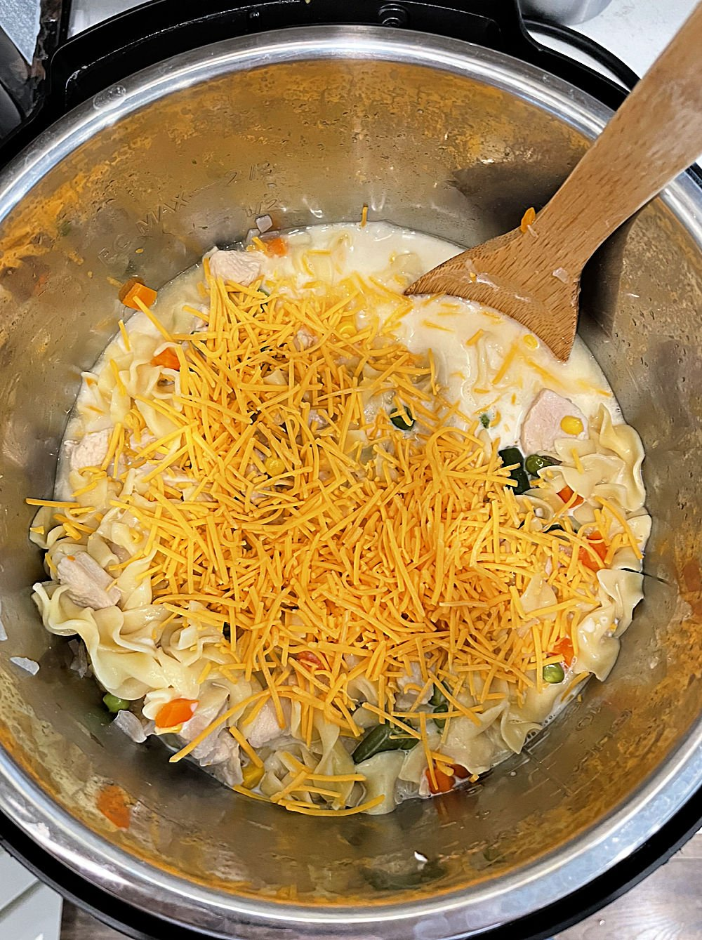 cheese mixed in with noodles and vegetables and chicken in pressure cooker