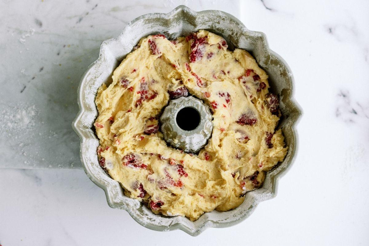 Fresh Raspberries mixed into cake batter in bundt cake pan