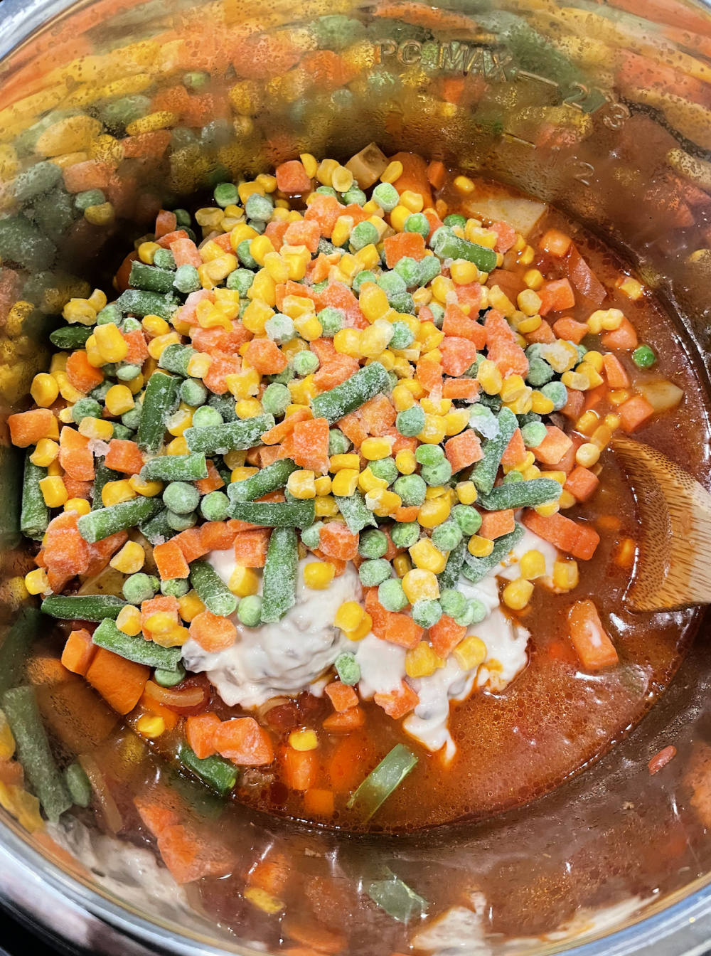frozen mixed vegetables being mixed into beef stew in instant pot