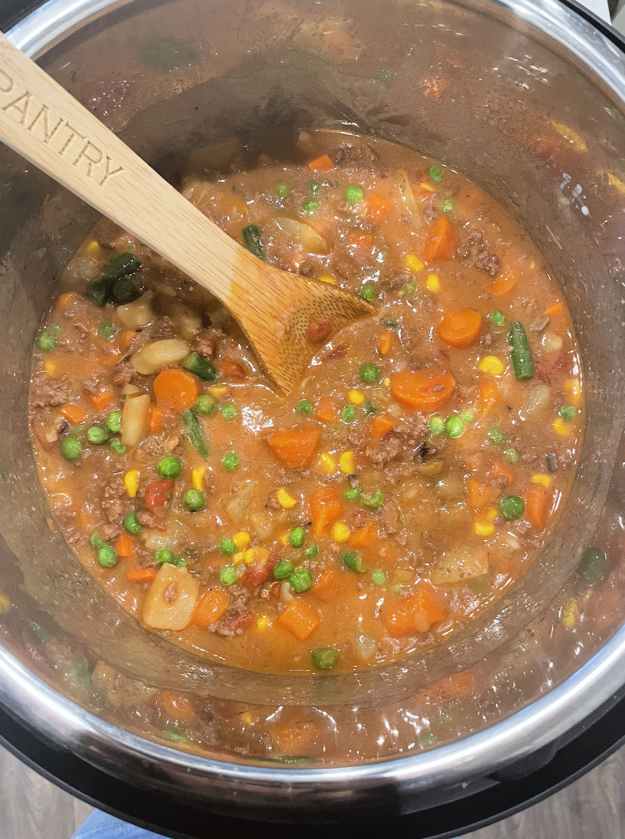ground beef vegetable stew being mixed with a wooden spoon in instant pot