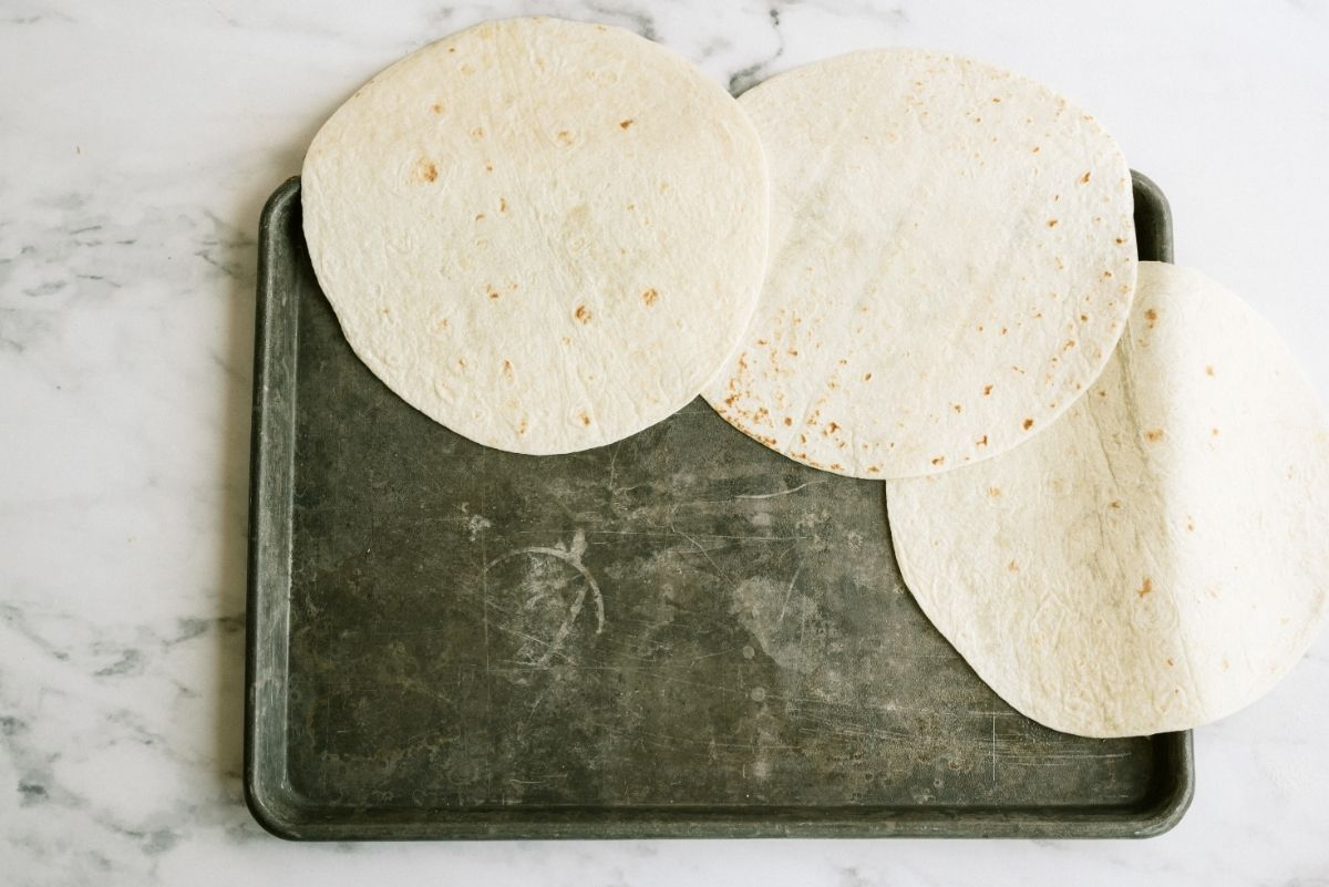Line the edge of cookie sheet with tortillas for Sheet Pan Ground Beef Quesadillas Recipe