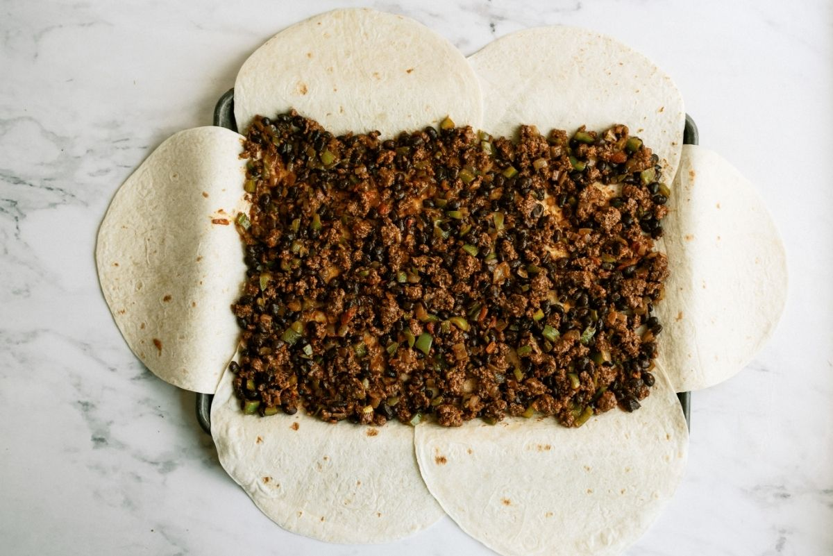 Meat mixture on top of tortillas for Sheet Pan Ground Beef Quesadillas Recipe