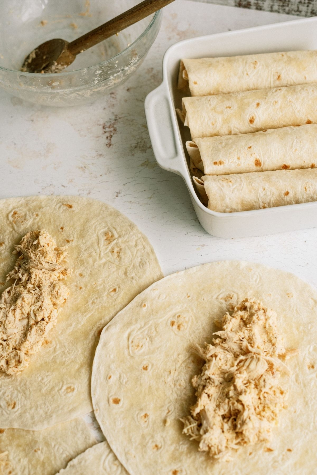 filled tortillas for Chimichangas, some rolled in dish others laying flat