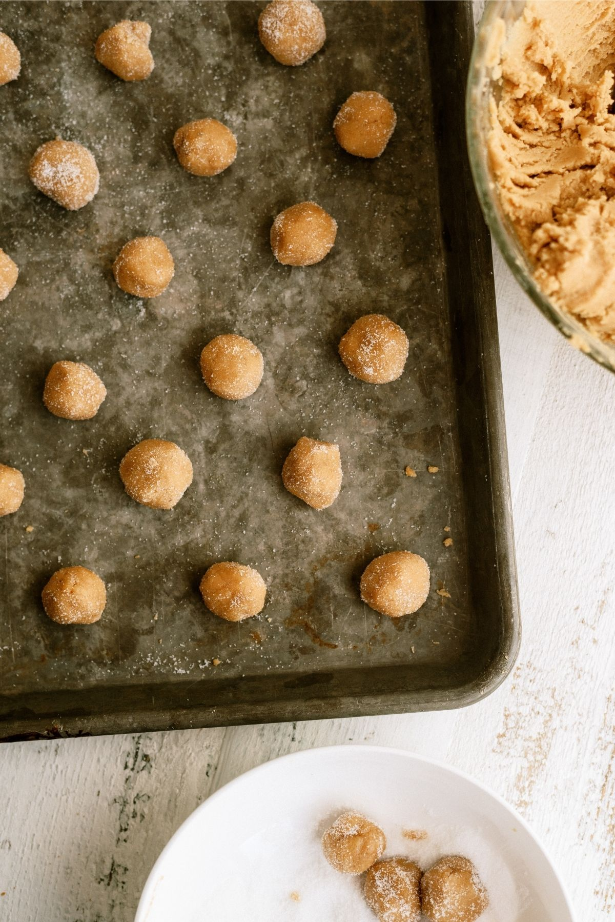Peanut butter cookie dough rolled into balls on cookie sheet