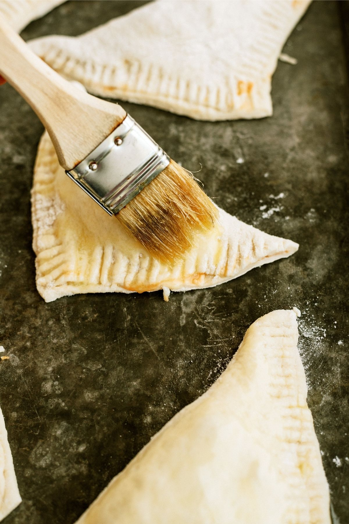 Brushing unbaked calzones with melted butter