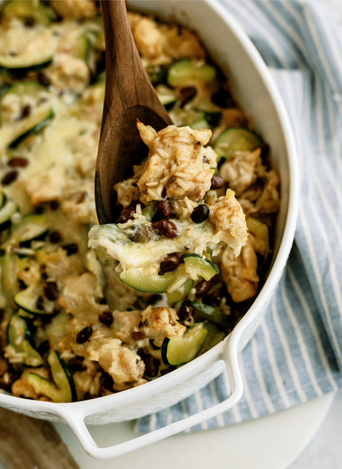 Chicken and Black Bean Casserole in a white casserole dish with a wooden spoon