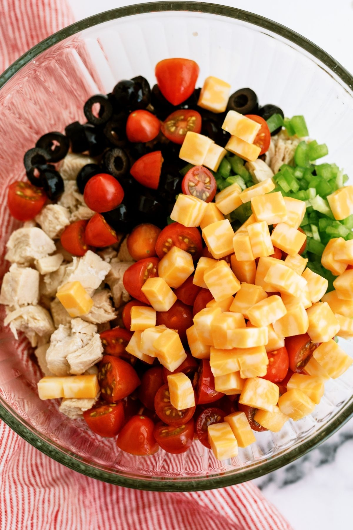 Ingredients for Grilled Chicken Bow Tie Pasta Salad mixed in a glass bowl
