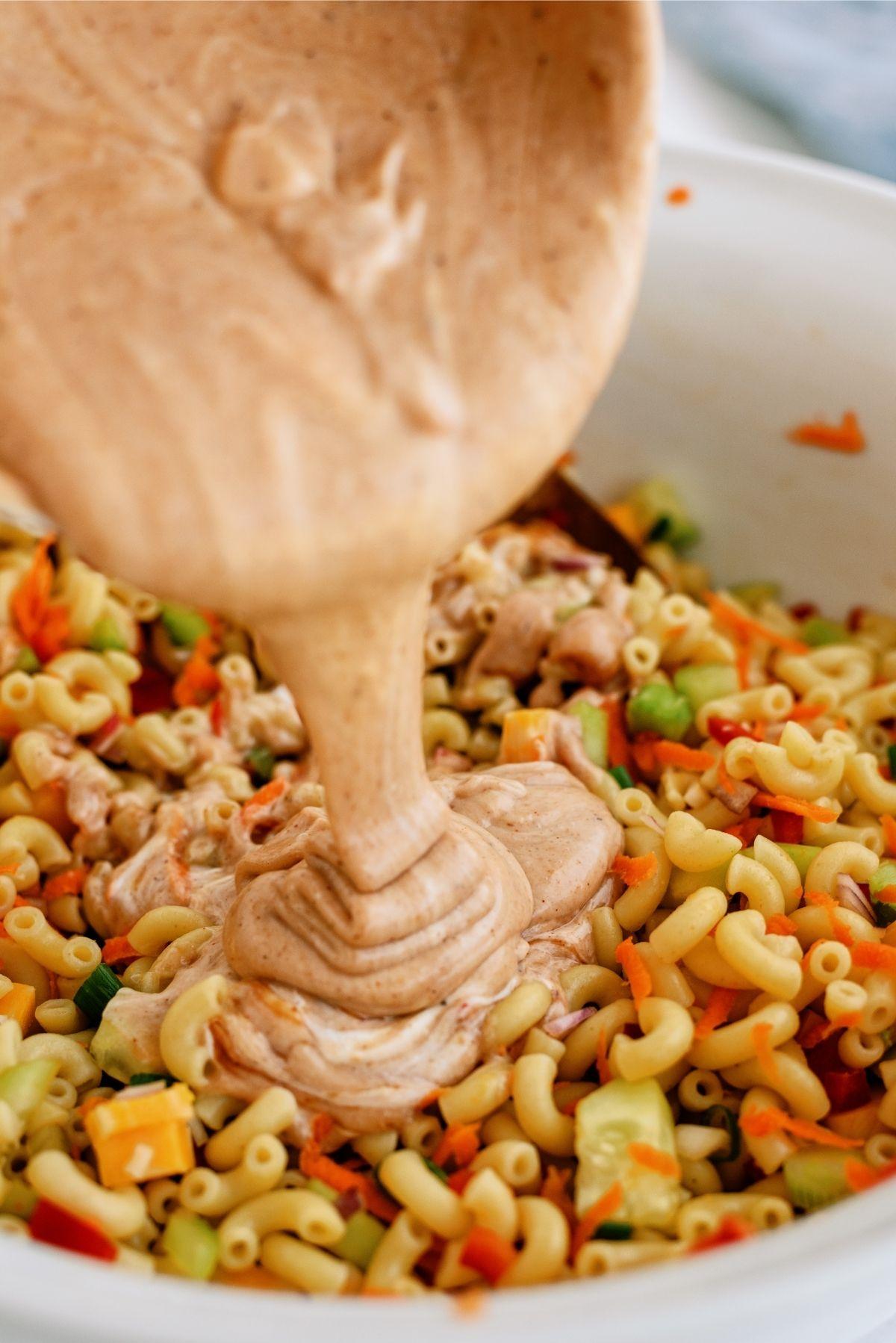Pouring sauce on BBQ Macaroni Salad