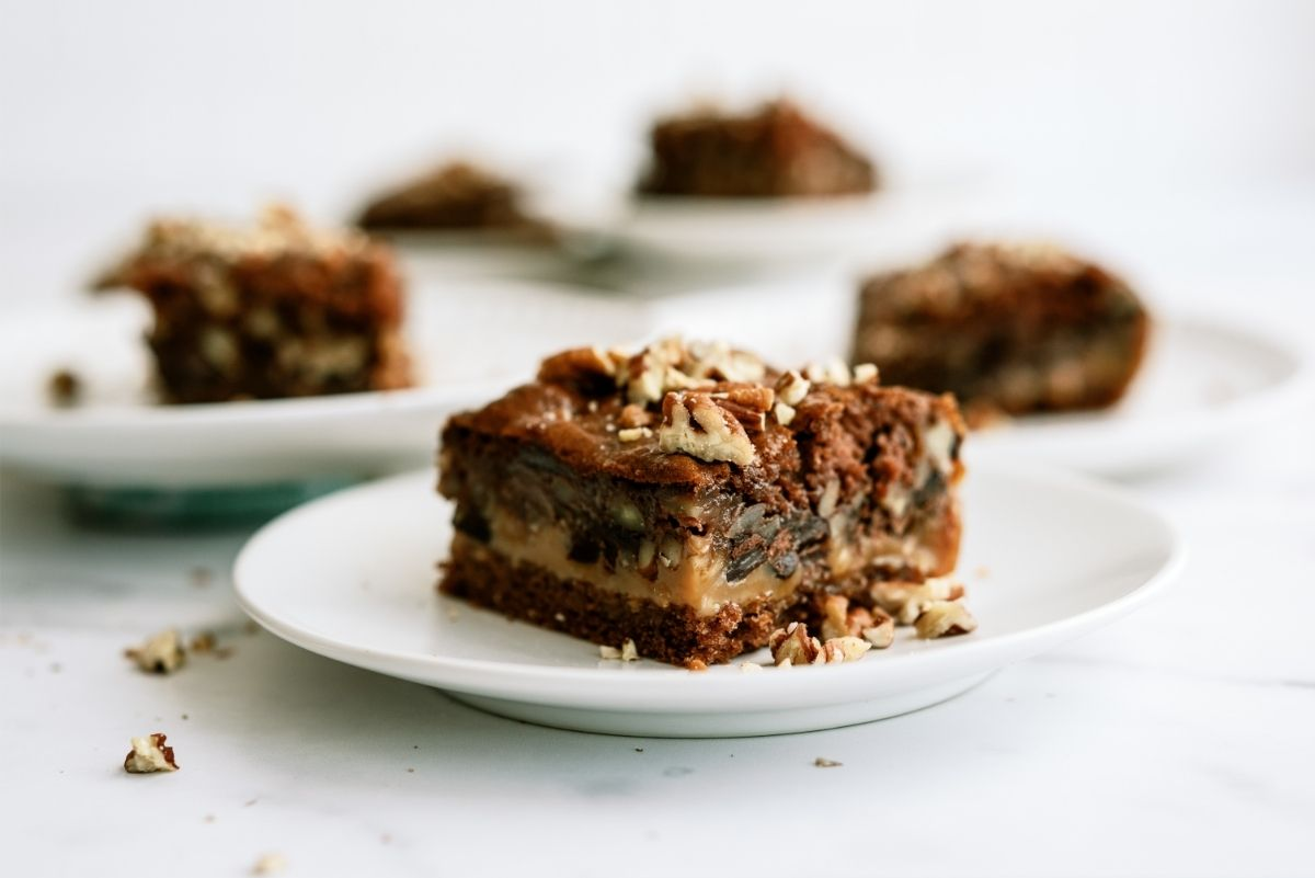Snickers Cake (Gooey Caramel Chocolate Cake) Recipe on a white plate