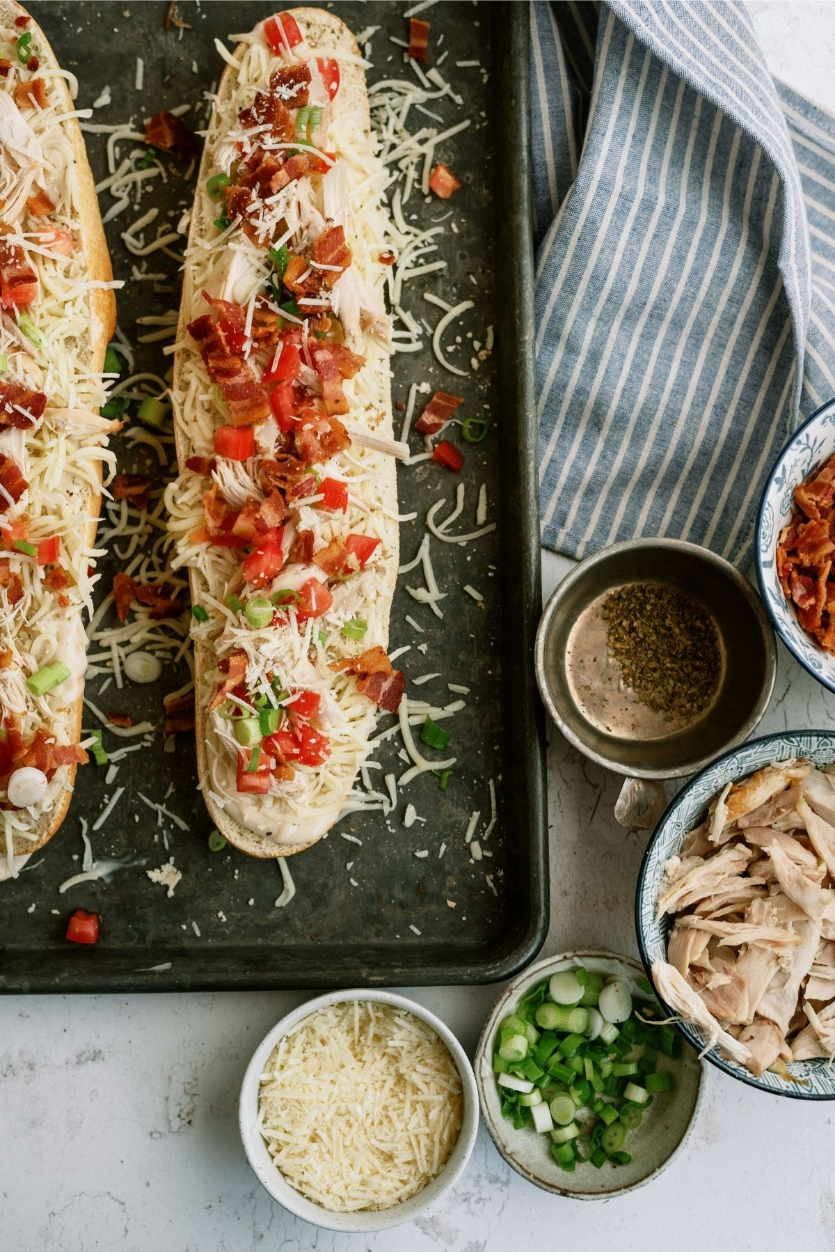 Unbaked Chicken Bacon Alfredo French Bread Pizza on a sheet pan