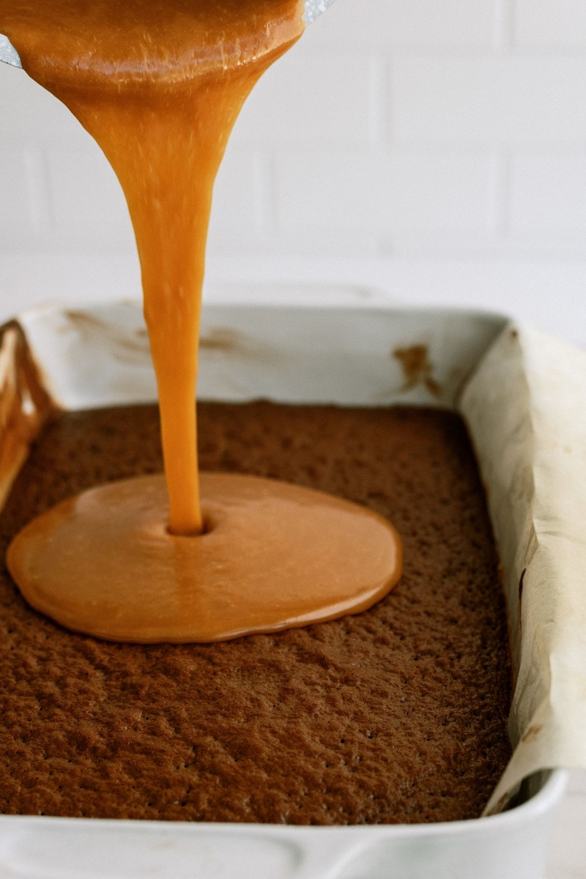 pouring caramel sauce on baked layer of cake