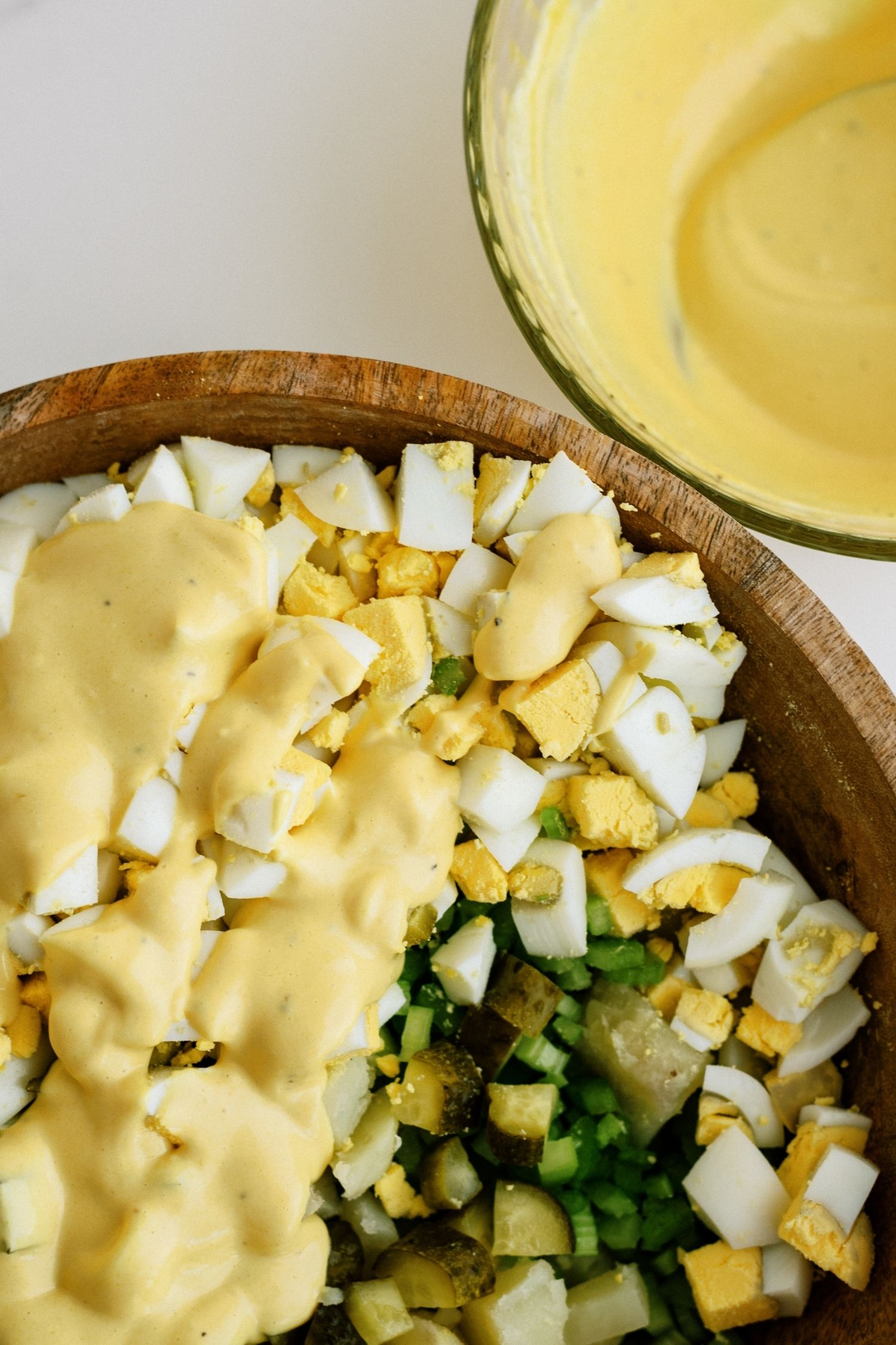 pouring mayo mixture on potato salad ingredients in a large bowl