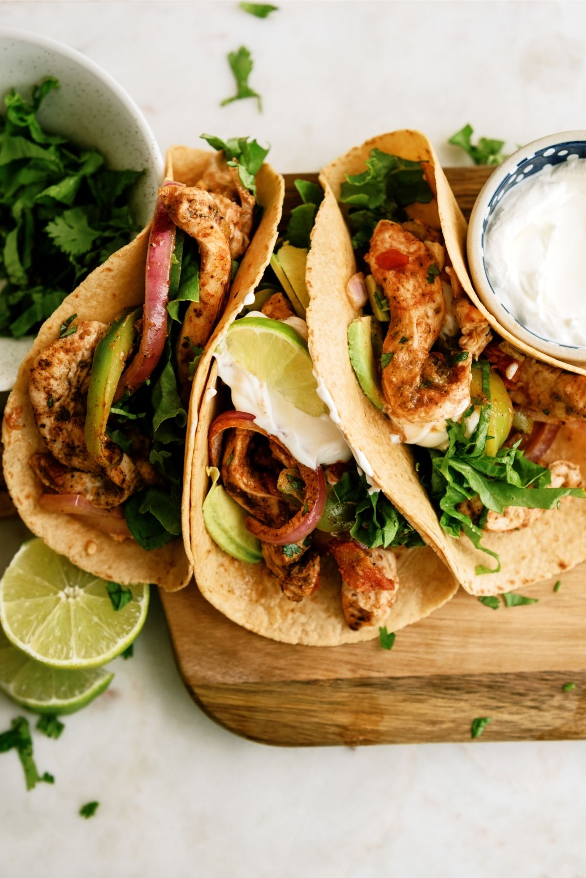 Baked Chicken Fajitas in tortillas, topped with a lime wedge and side of sour cream