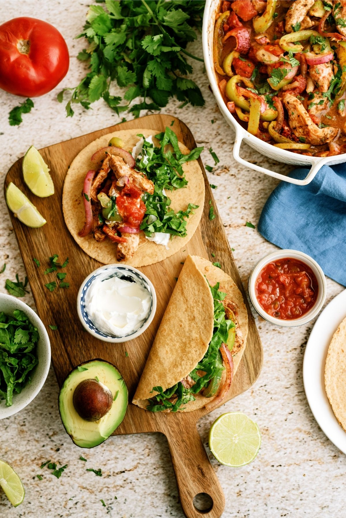 Baked Chicken Fajitas on a cutting board in tortillas surrounded by toppings