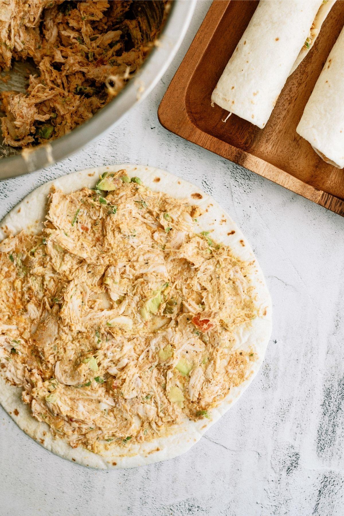 Thin layer of cream chicken mixture spread on tortilla